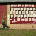 Erin Schneider with soil quilt displayed on barn