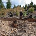 researcher near excavated forest soil