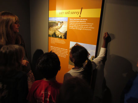 A group reads a soils information sign together