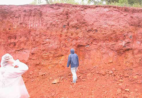 Person viewing a wall of red soil
