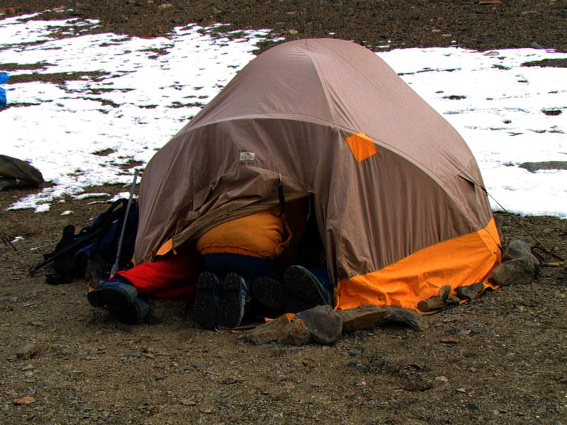 Three pairs of legs sticking out of a tent