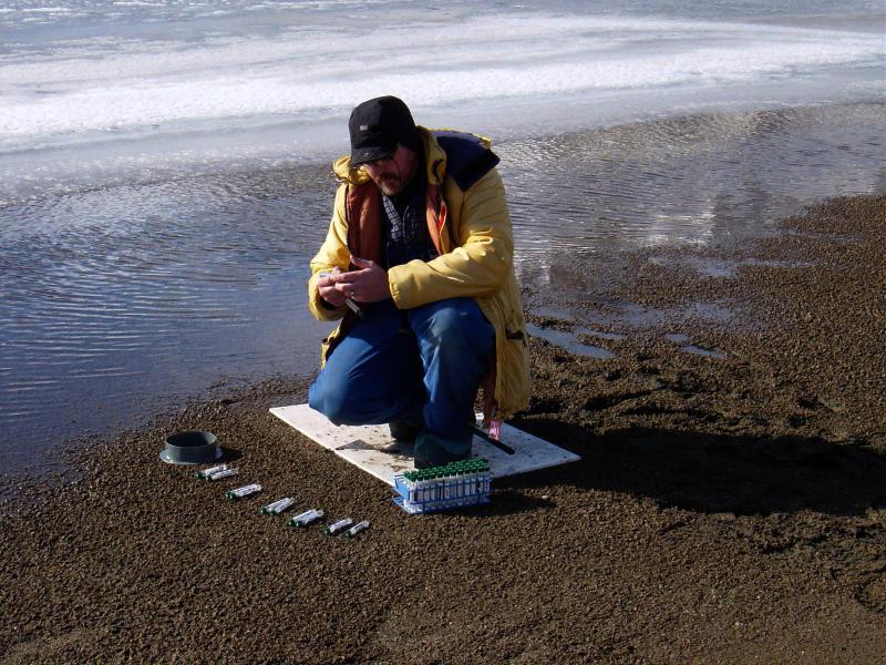 Scientist sampling next to a lake